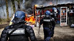 French gendarmes advance towards a burning make-shift shelter af