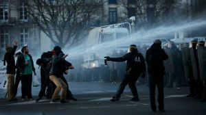 Masked protesters are sprayed by a water canon during clashes with French CRS riot police at a march in Nantes, western France, to demonstrate against the construction of a new airport in Notre-Dame-des-Landes